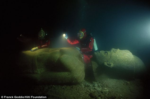Franck Goddio and divers from his team inspect the statue of a pharaoh